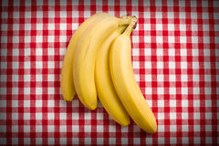 Yellow bananas on checkered tablecloth Stock Photo