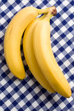 Yellow bananas on checkered tablecloth Stock Image