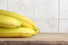 Yellow bananas. A composition with some yellow bananas on a wooden chopping board, inside a kitchen, space for text on the right, landscape cut Stock Photos