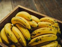 Yellow bananas. Fresh ripe yellow bananas in wicker basket on wooden background Stock Photo