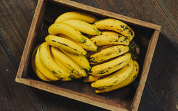 Yellow bananas. Fresh ripe yellow bananas in wicker basket on wooden background Royalty Free Stock Images