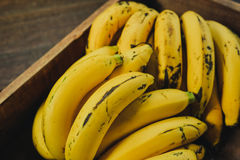 Yellow bananas. Fresh ripe yellow bananas in wicker basket on wooden background Royalty Free Stock Photo