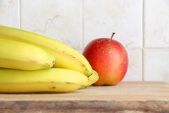 Yellow bananas and a red apple. A composition with some yellow bananas and a red apple on a wooden chopping board, inside a kitchen, landscape cut Royalty Free Stock Photos