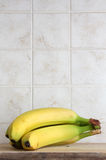 Yellow bananas. Some yellow bananas on a wooden chopping board, inside a kitchen, space for text on top, portrait cut Stock Images