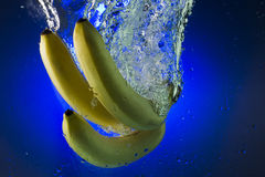 Yellow bananas in water on a blue background Royalty Free Stock Photography