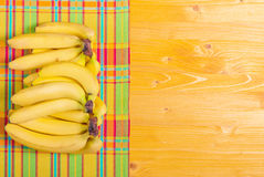 Yellow bananas on a yellow napkin color board to the right place Royalty Free Stock Image