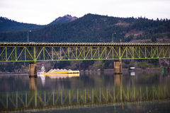 Yellow barge under the bridge across the river Royalty Free Stock Images