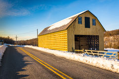 Yellow barn and a snow covered field along a country road in Yor Royalty Free Stock Photo