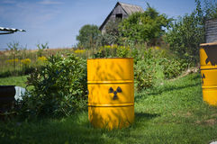 Yellow barrels with a sign of radiation. On the lawn stock photo