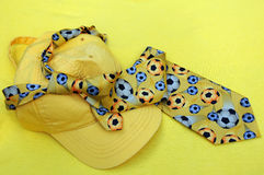 Yellow Baseball Cap and Necktie. Yellow baseball cap and tie with soccer balls on it on a yellow background for the upcoming FIFA soccer world cup in South Royalty Free Stock Images