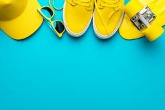 Yellow baseball cap, sunglasses, sneakers, mini cruiser board on blue background. Top view of yellow modern teenage accessories. Flat lay image of yellow stock photo