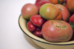 Yellow basin with black rim, overfull with red sweet vegetables. Emphasis on tomato Royalty Free Stock Photos