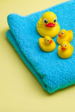 Yellow bath duck on blue towel Royalty Free Stock Photos