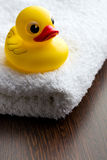 Yellow bath duck on white towel Royalty Free Stock Images