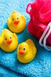 Yellow bath ducks and bath puff Royalty Free Stock Photo