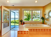 Yellow bathroom with lake view and large tub. Stock Photos
