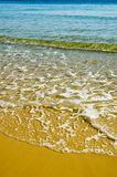 Yellow Beach. Yellow sandy beach with small, clear, blue-green waves Stock Images
