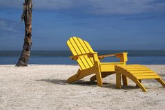 Yellow Beach Chair. A inviting scene of a comfortable yellow beach chair on a tropical beach Stock Images
