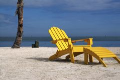 Yellow Beach Chair. A wooden yellow recliner sits on a beautiful tropical beach Royalty Free Stock Image