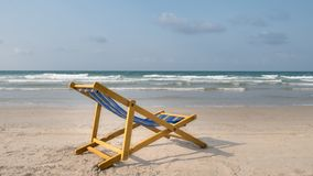 An yellow beach chair rests on the white sand of the beach and B