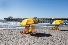 Yellow Beach Chairs under Umbrella South Carolina. Yellow beach chairs under a sun umbrella on the shore of Folly Beach near the pier in Charleston, South Royalty Free Stock Images