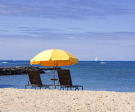 Yellow beach umbrella. With deck chairs on sandy beach with blue sea and sky Stock Photography