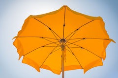 Yellow beach umbrella under the sun near the sea Royalty Free Stock Images