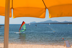 Yellow Beach Umbrella, WindSurfer, Hills and Sea in background Stock Photography