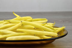 Yellow bean pods on the glass plate, detail. Yellow bean pods Stock Photo