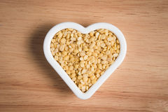 Yellow bean seed in a heart shape block. On a wood background Stock Photography