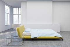 Yellow bed, concrete floor side Stock Photo