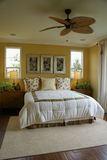 Yellow Bed Room with Fan Stock Photo