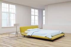 Yellow bed, wooden floor corner view Stock Photos