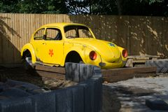Yellow Beetle Shell. Volkwagon Beetle shell parked in a garden royalty free stock image