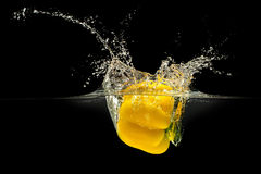 Yellow bell pepper falling in water with splash on black background Royalty Free Stock Images