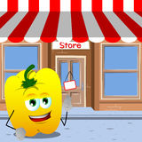 Yellow bell pepper with fingers crossed in front of a storefront Royalty Free Stock Images