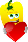 Yellow bell pepper holding a big red heart Stock Photo