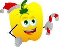 Yellow bell pepper holding a candy cane and wearing Santa's hat Royalty Free Stock Photos