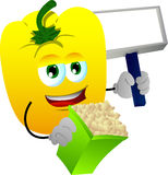 Yellow bell pepper holding popcorn and blank board Royalty Free Stock Photo