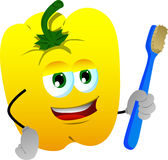 Yellow bell pepper holding tooth brush Stock Photo