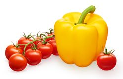 Yellow bell pepper and red cherry tomatoes with green leaves Royalty Free Stock Images