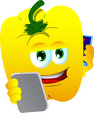 Yellow bell pepper speaking on a smartphone while reading a tablet Stock Image