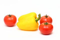 Yellow bell pepper and three tomatoes Stock Photos