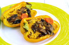 Yellow bell peppers stuffed with mushrooms, vegetables Stock Photo