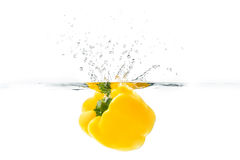 Yellow bellpepper dropped into the water with water splash on a. White background Royalty Free Stock Photography