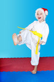With the yellow belt a little girl beats a kick leg. With the yellow belt a girl beats a kick leg royalty free stock images