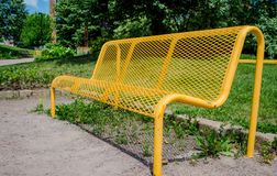 Yellow bench. The bench is made of steel and painted in bright yellow color stock photography