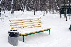 Yellow bench and trashcan in snow Stock Photos