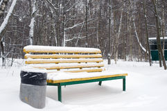 Yellow bench and trashcan in winter Royalty Free Stock Photo