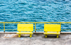 Yellow Benches by Blue Water Stock Photo